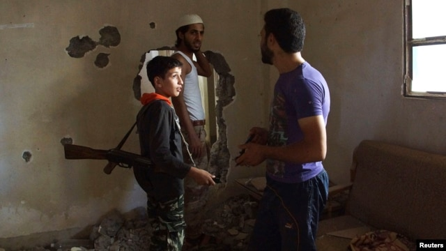 A 14-year-old fighter, whom activists say is the youngest in the Khadraa brigade operating under the Free Syrian Army, chats with his fellow fighters in Deir al-Zor, July 9, 2013.