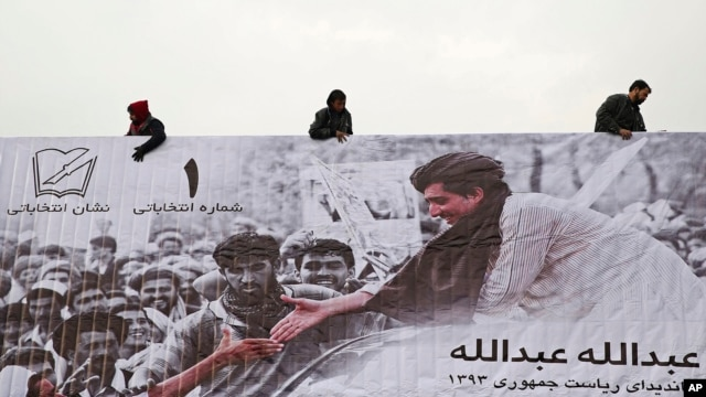 Afghans erect an election poster of presidential election candidate, Abdullah Abdullah in Kabul, Afghanistan, Feb. 2, 2014.