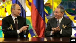 Russia's President Vladimir Putin, left, and Cuba's President Raul Castro applaud at Revolution Palace in Havana, Cuba, July 11, 2014.
