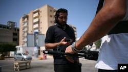 Men stand guard at an anti-Gadhafi checkpoint in downtown Tripoli, August 27, 2011