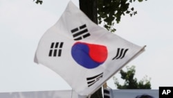 FILE - The South Korean flag flies at a protest in Seoul, South Korea, July 20, 2018.