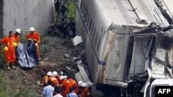 Nhân viên cứu hộ khiêng xác một nạn nhân ra khỏi đống đổ nát của đoàn tàu cao tốc bị rơi từ một cây cầu ở thành phố Ôn Châu, tỉnh Chiết Giang, Trung Quốc, ngày 24/7/2011