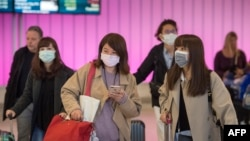 Passengers wear protective masks to protect against the spread of the Coronavirus as they arrive at the Los Angeles International Airport, California, on January 22, 2020.