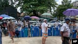 缅甸仰光居民排队等候给氧气管充气以救治新冠病人。(2021年7月11日)