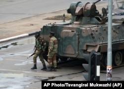 FILE: A military tank is seen with armed soldiers on the road leading to President Robert Mugabe's office in Harare, Zimbabwe Wednesday, Nov. 15, 2017