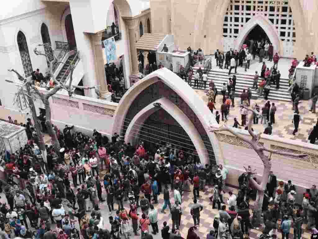 Pessoas à porta da igreja depois do ataque suicida à bomba na cidade de Tanta no Delta do Nilo