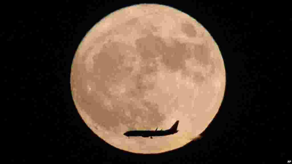 Un avion vole à coté la lune vu à Beijing, Chine, le 14 novembre 2016.