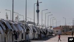 Seorang pengungsi berjalan di Oncupinar, tempat perkampungan pengungsi Suria dekat kota perbatasan Kilis di Turki (17/3).
