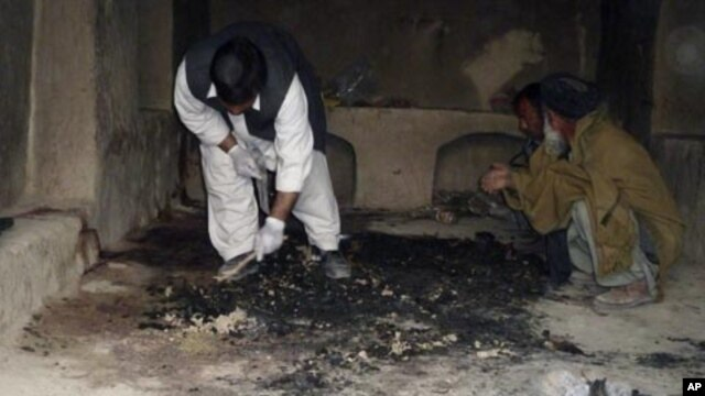 Afghan men investigate at the site of a shooting incident, apparently by a lone U.S. Army sergeant that killed 16 civilians on Sunday, in Kandahar province, March 11, 2012.