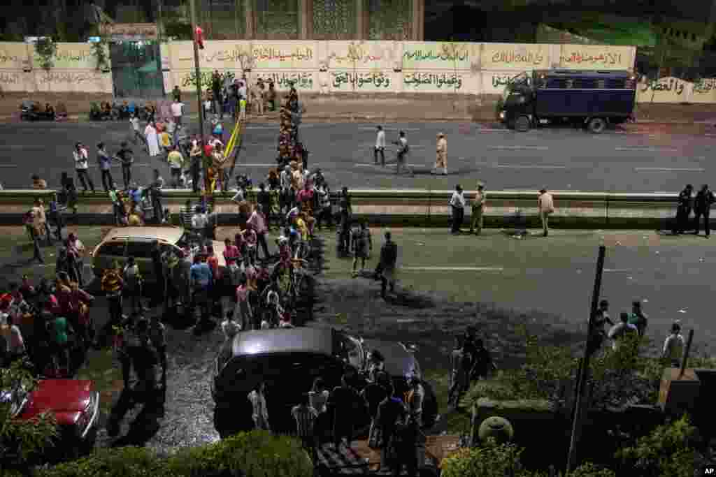 Egyptians gather outside of a national security building after a bomb exploded in the Shubra el-Kheima neighborhood of Cairo injuring several people according to security officials, early Aug. 20, 2015.