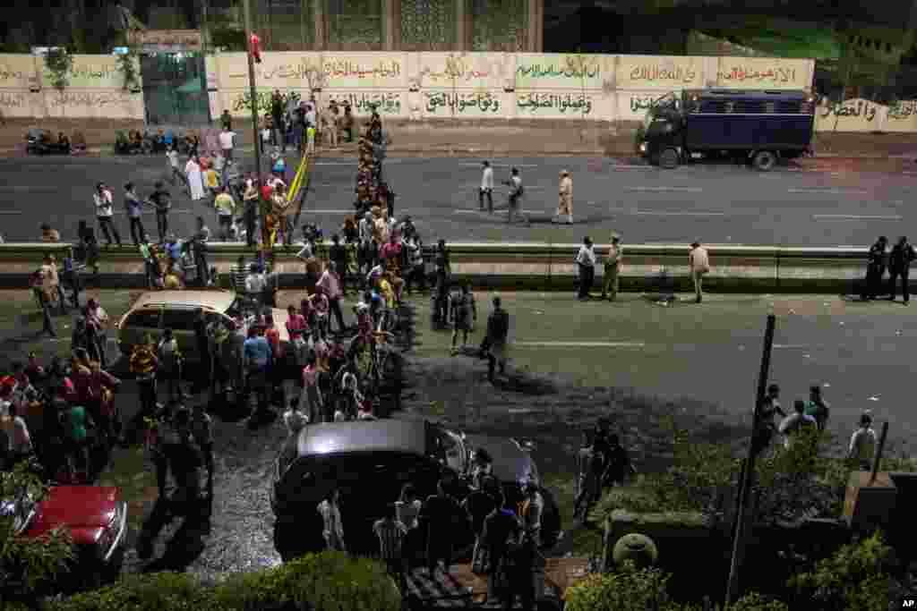 Warga berkumpul di luar sebuah bangunan keamanan nasional setelah bom meledak di daerah Shubra el-Kheima di Kairo yang melukai beberapa orang menurut para pejabat keamanan (20/8). (AP/Ibrahim Ezzat)