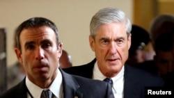 Công tố viên đặc biệt Robert Mueller (phải) rời đi sau khi báo cáo cho các thành viên Thượng viện Hoa Kỳ về cuộc điều tra của ông về sự thông đồng khả dĩ giữa ban vận động tranh cử của Donald Trump với Nga trong cuộc bầu cử tổng thống năm 2016