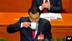El primer ministro chino Li Keqiang bebe de la taza mientras entrega el informe de trabajo en la sesión de inauguración de la Asamblea Popular Nacional anual en el Gran Salón del Pueblo de Pekín, el domingo 5 de marzo de 2017.