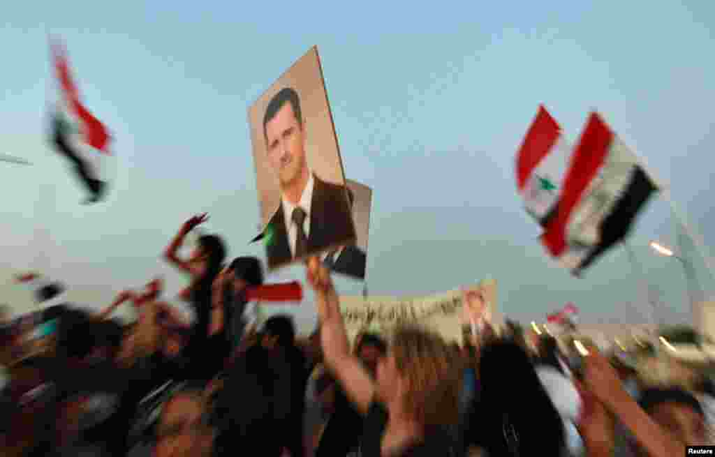 Jordanians and Syrians living in Jordan hold pictures of President Bashar al-Assad and shout slogans against the Syrian Revolution during a demonstration near the Syrian embassy in Amman July 19, 2012.