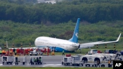A Boeing passenger plane from China, a Xiamen Air, sits on the grassy portion of the runway of the Ninoy Aquino International Airport after it skidded off the runway while landing, Aug. 17, 2018 in suburban Pasay city southeast of Manila, Philippines. All the passengers and crew of Xiamen Air Flight 8667 were safe and were taken to an airport terminal, where they were given blankets and food before being taken to a hotel.