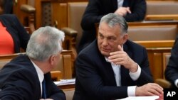 Hungarian Prime Minister Viktor Orban, right, chats with his deputy Zsolt Semjen during a plenary session of the Parliament in Budapest, Hungary, Budapest, Hungary, Monday, March 30, 2020. (Zoltan Mathe/MTI via AP)