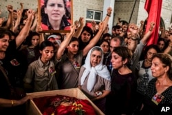 Mourners chant slogans as they gather around the body of Gulay Ozarlan, a DHKP-C militant, who was killed during a major police sweep that was launched against the outlawed group as well as suspected members of the outlawed Kurdish rebel group, and also Islamic State group militants, during her funeral In Istanbul, Turkey, July 25, 2015.