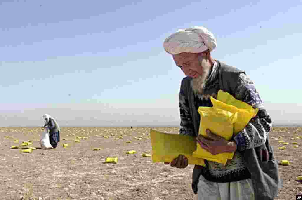 2001年10月13日,阿富汗当地居民在阿富汗北部的田野里拾起美国空投的人道救援物资。