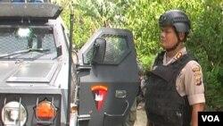 Kapolres Poso AKBP Susnadi berdiri di sisi kendaraan yang terkena tembakan. (VOA/Yoanes Litha)