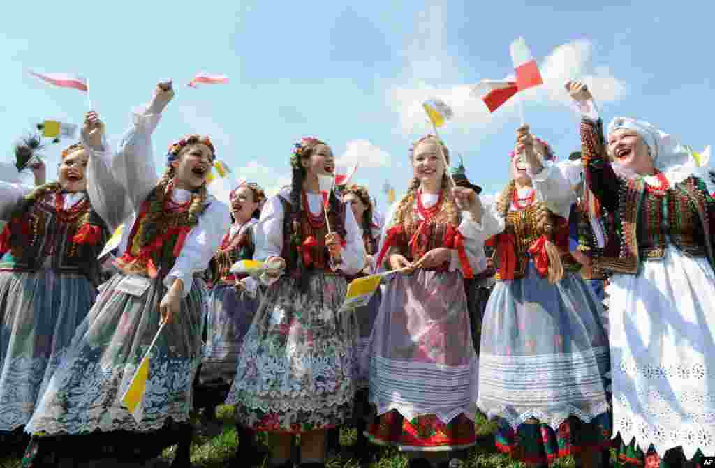 A group of folk dancers rehearse prior to the arrival of Pope Francis at the military airport in Krakow, Poland. Pope Francis is in Poland to meet young Catholics from around the globe and visit the Auschwitz death camp and many Catholic places in this deeply religious nation.