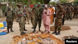 FILE - Military officials stand near ammunition seized from suspected members of Hezbollah after a raid of a building in Nigeria's northern city of Kano on May 30, 2013.