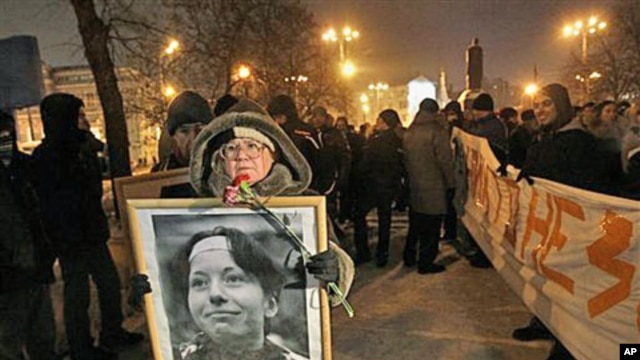 A demonstrator holds a portrait of slain reporter Anastasiya Baburova during a memorial rally in downtown Moscow, held in memory of rights lawyer Stanislav Markelov and Baburova, who were shot in broad daylight on a street near the Kremlin two years ago,