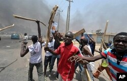 People holding wooden and metal sticks demonstrate in Nigeria's northern city of Kano where running battles broke out between protesters and soldiers on Monday.
