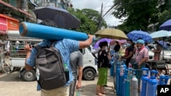 A man carries an oxygen tank while others line up with their oxygen tanks outside an oxygen refill station in Pazundaung township in Yangon, Myanmar, Sunday, July 11, 2021. Myanmar is facing a rapid rise in COVID-19 patients and a shortage of oxygen supplies just as the country i