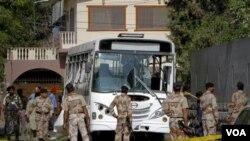 Sòlda pakistanè ki rasanble devan rès bis ki te eksploze nan Karachi, nan Pakistan madi 26 avril 2011 la (AP Photo/Shakil Adil)