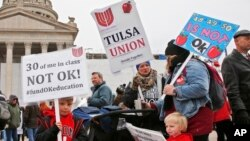 Keagan Nedrow, left, and Reed Nedrow, bottom right, stand with their mother, Tara Nedrow, right, who teaches history at Union High School, and other teachers, during a teacher rally against low school funding at the state Capitol Oklahoma City, Monday, Ap