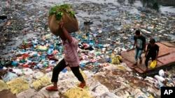 Seorang pria membawa sekarung sayur-sayuran berjalan melewati kanal yang dipenuhi oleh sampah plastik dan sampah-sampah lainnya di Mumbai, India. (Foto:Dok)