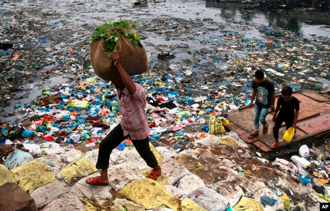 FILE - A man carries a sack of vegetables as he walks past a polluted canal littered with plastic bags and other garbage in Mumbai, India.