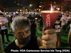 参与六四31周年维园烛光集会的市民高举烛光,为六四屠城死难者默哀一分钟 (美国之音/汤惠芸)