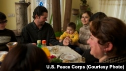 A family in Georgia shares a meal with a U.S. education volunteer.