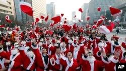 24일 성탄절을 맞아 서울에서 열린 자선행사에서 산타클로스 복장의 자원봉사자들이 모자를 머리 위로 던지고 있다. 봉사자들은 빈곤 가정에 성탄절 선물을 전달했다.