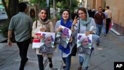 Partidarias del presidente iraní, Hassan Rouhani, portan carteles con su foto en las calles de Teherán, durante la campaña para la votación del viernes, 19 de mayo de 2017.