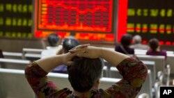 Một nhà đầu tư nhìn màn hình hiển thị giá cổ phiếu ở một trung tâm chứng khoán tại Bắc Kinh ngày 21/8/2015.