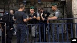 Polisi Israel memeriksa dokumen seorang pria yang berusaha memasuki kota tua Yerusalem hari Minggu (4/10). Israel mencabut peraturan keamanan ketat hari Selasa 6/10.