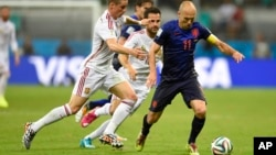 Netherlands' Arjen Robben, right, is challenged by Spain's Fernando Torres during the World Cup match between Spain and the Netherlands, June 13, 2014.