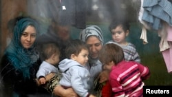 Syrian refugees look through a window inside a refugee center. (File)