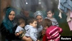 Sirijske izbjeglice gledaju kroz prozor unutar izbjegličkog centra dok čekaju na podjelu humanitarne pomoći volontera bugarskog Crvenog križa u Sofiji 17. prosinca 2013. REUTERS / Stoyan Nenov