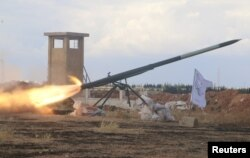 FILE - Rebel fighters from the First Regiment, part of the Free Syrian Army, fire a Grad rocket from Aleppo's al-Haidariya neighborhood, toward forces loyal to Syria's President Bashar al-Assad stationed in Talet al-Sheikh Youssef, Syria, May 29, 2016.