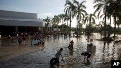 Habitantes de Acapulco caminan en un estacionamiento con el agua hasta la cintura en Punta Diamante, México.