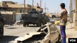 Seorang remaja memperhatikan pasukan Irak melewati daerah yang baru saja direbut dari kekuasaan ISIS di Mosul, Kamis (1/6).