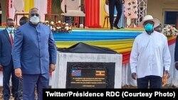 Perezida Félix Tshisekedi na Yoweri Museveni bahagaze iruhande rw'ibuye ry'ifatizo ry'umuhanda ibihugu byombi bihuriyeho ugiye kubakwa.
