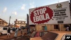 Des piétons passent une affiche de campagne contre la maladie à virus Ebola à Freetown, Sierra Leone, 15 janvier 2015