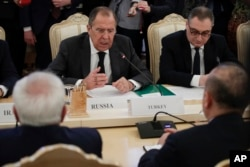 FILE - Russian Foreign Minister Sergey Lavrov, center, gestures while speaking to Turkey's Foreign Minister Mevlut Cavusoglu, right, back to a camera, and Iranian Foreign Minister Mohammad Javad Zarif, left, back to a camera, during their talks in Moscow, Russia.