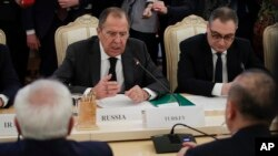 Russian Foreign Minister Sergey Lavrov, center, gestures while speaking to Turkey's Foreign Minister Mevlut Cavusoglu, right, back to a camera, and Iranian Foreign Minister Mohammad Javad Zarif, left, back to a camera, during their talks in Moscow, Russia, Dec. 20, 2016.