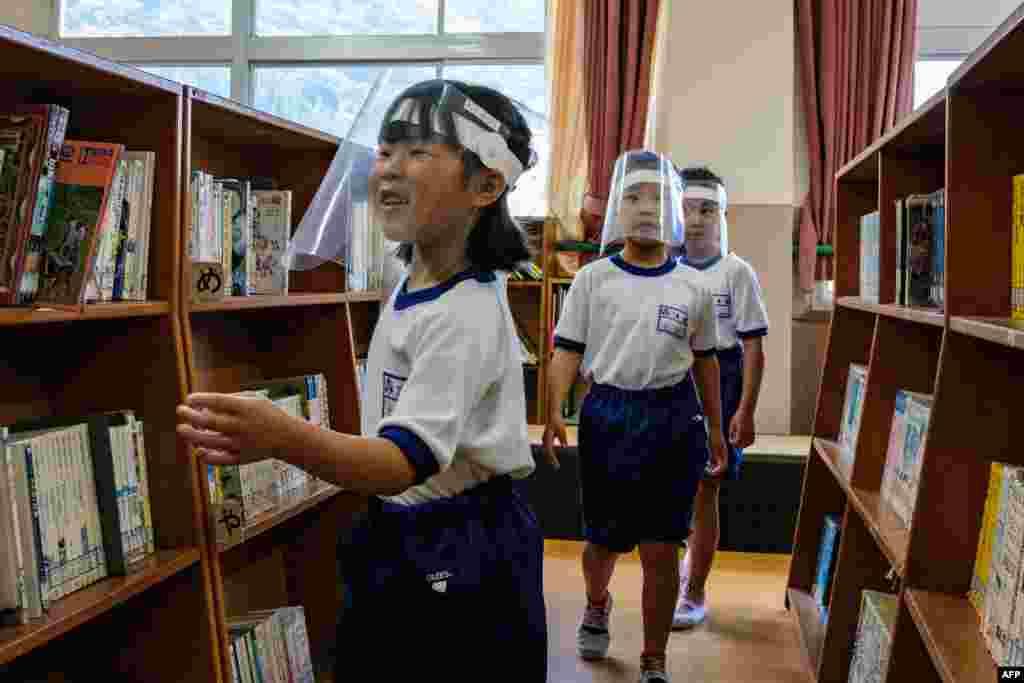 Students wearing face shields visit the library in Kinugawa Elementary School in Nikko, Tochigi Prefecture, Japan.