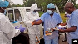 Health workers are handed personal protective gear by a team leader, right, before collecting the bodies of the deceased from streets in Monrovia, Liberia, Saturday, Aug. 16, 2014. New figures released by the World Health Organization showed that Liberia